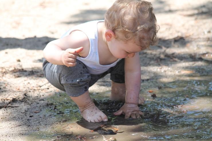 Toddler playing in mud